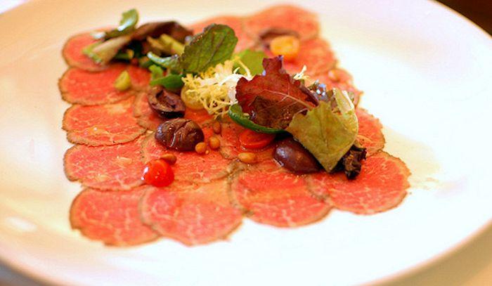 Carpaccio di vitello con olive e pinoli