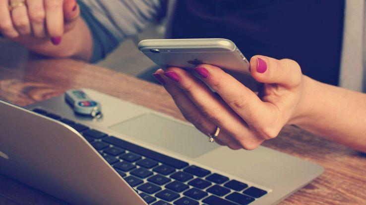 Un utente usa lo smartphone davanti a un PC