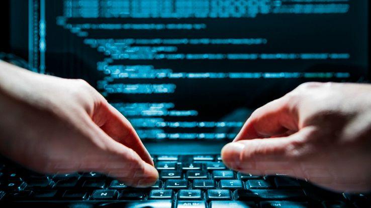 Hacker digita la tastiera di un laptop