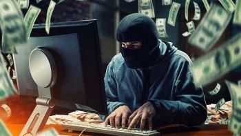 Hacker al lavoro circondato da soldi