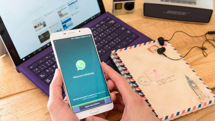 Un utente tiene in mano uno smartphone mentre lancia l'app di WhatsApp