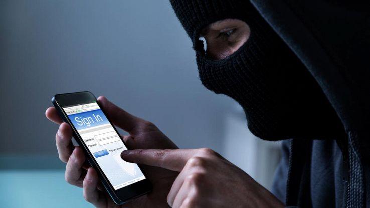 Un uomo incappucciato usa uno smartphone
