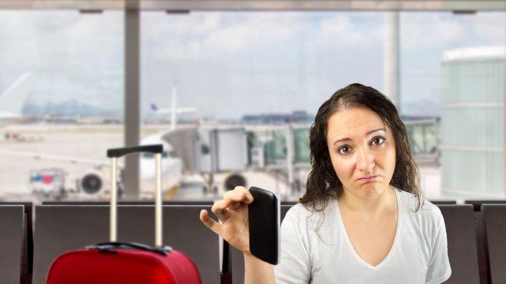 Donna triste in aeroporto con telefono in mano