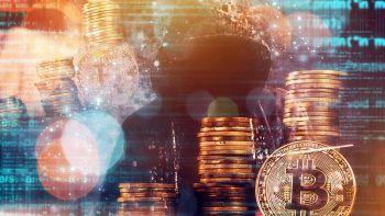 Un hacker davanti a tante monete di Bitcoin