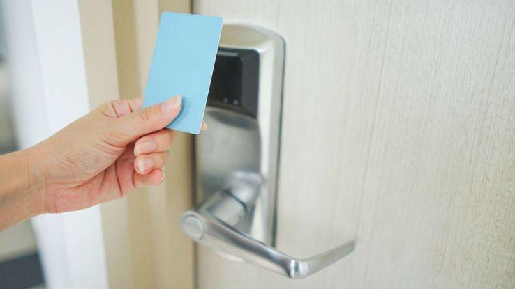 Una mano avvicina una chiave elettronica davanti alla serratura di una porta