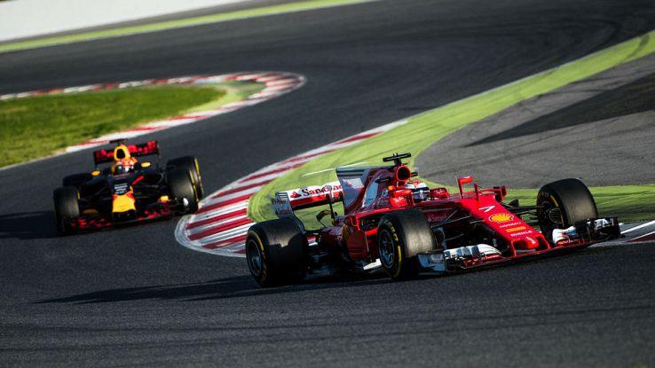 Una Ferrari precede una Red Bull in una curva a esse