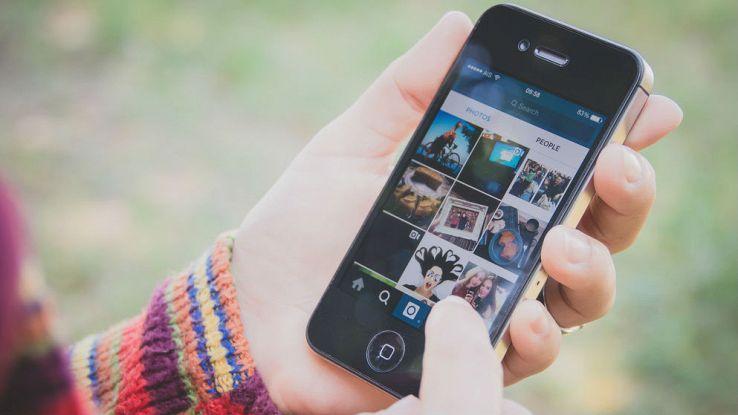 Primo piano di una mano che sfoglia un profilo del social media Instagram attraverso uno smartphone