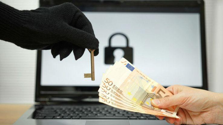 Una mano con un guanto porge una chiave a un'altra mano che porge dei contanti, nello sfondo un PC con l'immagine di un lucchetto