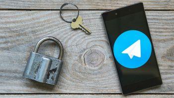 Un lucchetto, una chiave e uno smartphone con l'icona dell'app Telegram in evidenza