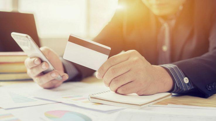 Un uomo tiene in mano una carta di credito e con l'altra usa uno smartphone