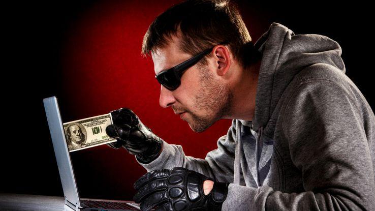 Un hacker in occhiali da sole inserisce una banconota sullo schermo di un PC