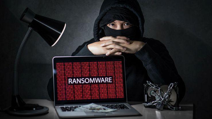 Un hacker incappucciato seduto su una scrivania con un computer davanti che espone la scritta in rosso ransomware