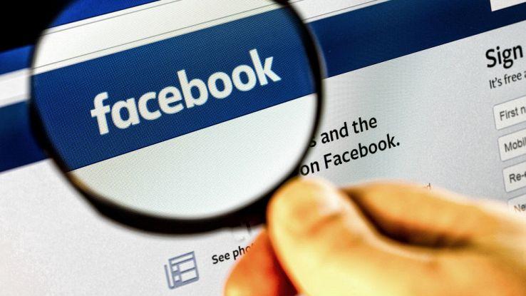 Una mano tiene una lente di ingrandimento che mette in evidenza la scritta Facebook