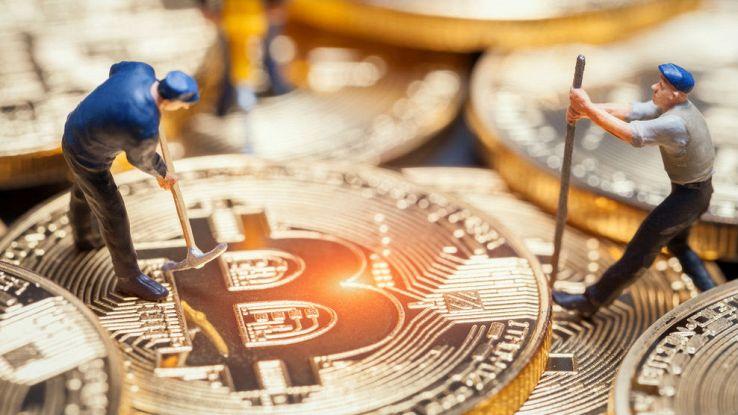 Due omini giocattolo lavorano su una moneta di Bitcoin