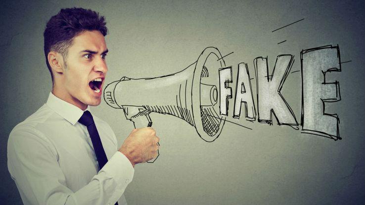 un ragazzo urla la parola Fake su un megafono disegnato
