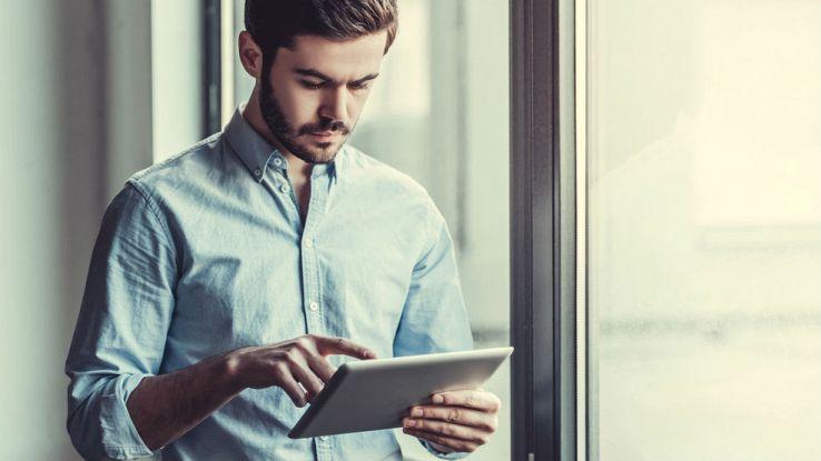 Un utente usa in piedi un tablet davanti a una finestra
