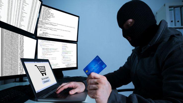 Un uomo incappucciato tiene in mano una carta di credito mentre manomette un PC