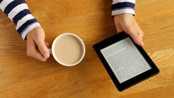 Una donna legge dal suo Kindle mentre beve una tazza di caffè