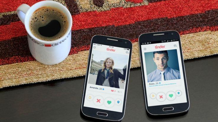 Due smartphone aperti sull'app Tinder e una tazzina di caffè su un tavolo