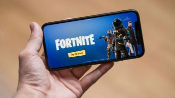 Un utente tiene in mano uno smartphone e sul display appare la schermata principale del videogame Fortnite