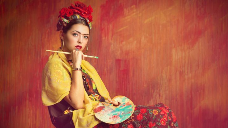 Una donna vestita da pittrice impersonifica l'artista Frida Khalo