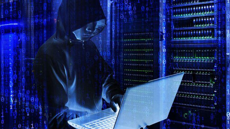 Un hacker incappucciato tiene in mano un computer