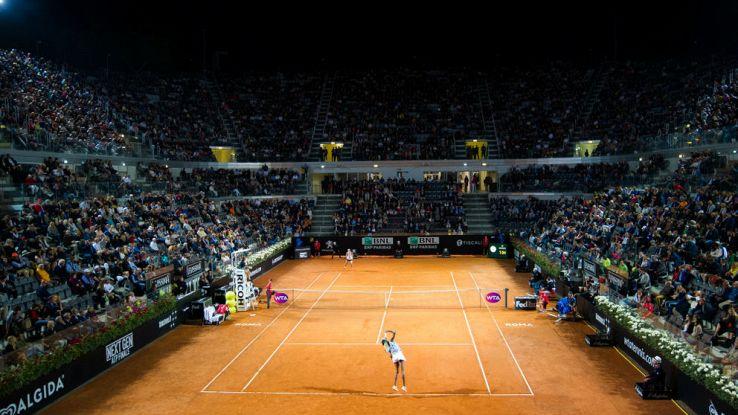 Una tennista si prepara alla battuta nella terra rossa di Roma agli Internazionali d'Italia