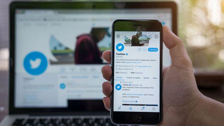 Uno smartphone in primo piano aperto sul social Twitter e uno PC sullo sfondo sempre collegato a Twitter