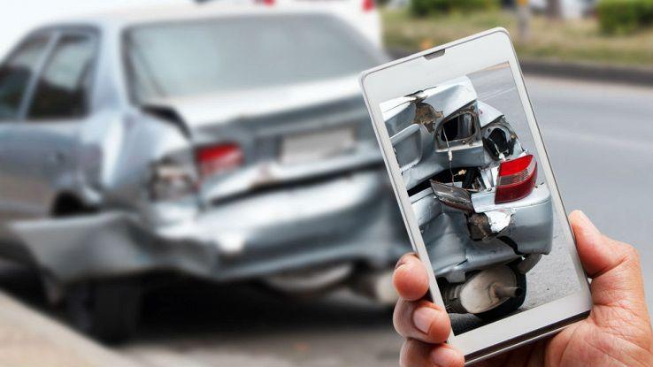 Un utente fotografa con lo smartphone una macchina incidentata