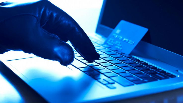 Una mano con un guanto sta cliccando dei tasti su un computer portatile con una carta di credito sopra la tastiera