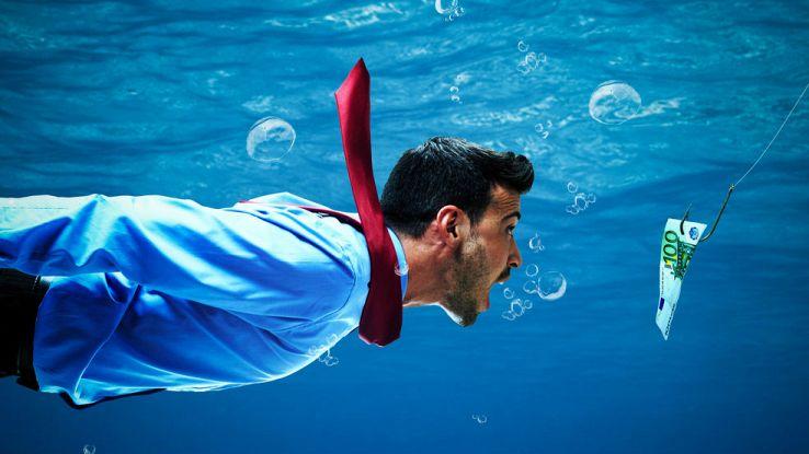 Un uomo in camicia e cravatta insegue dei soldi appesi a un amo sott'acqua