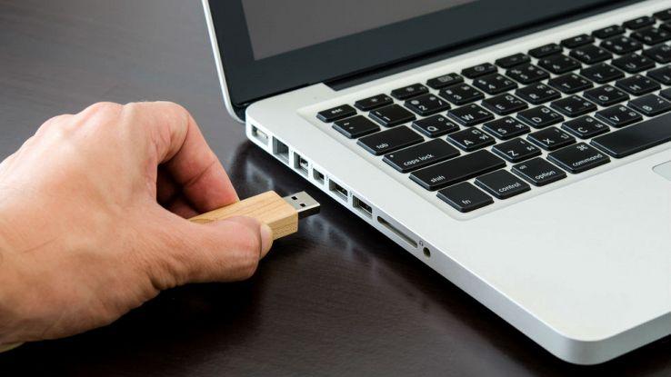 Un utente inserisce una pennetta USB su un computer portatile