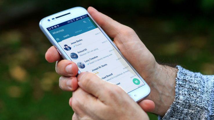 Un utente usa il proprio smartphone a due mani e visualizza la schermata delle chat di WhatsApp