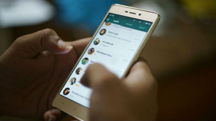 Una ragazza tiene in mano uno smartphone mentre utilizza WhatsApp