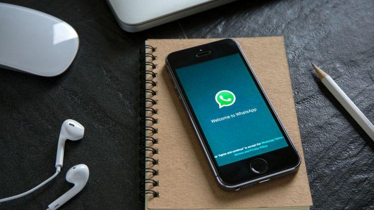 Un iPhone sulla schermata iniziale di WhatsApp posto sopra una scrivania con un blocco note e un paio di cuffiette