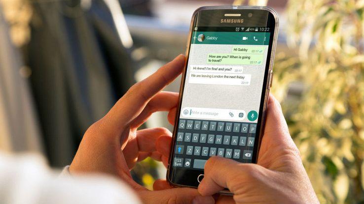 Una donna utilizza il proprio smartphone e legge una chat di WhatsApp