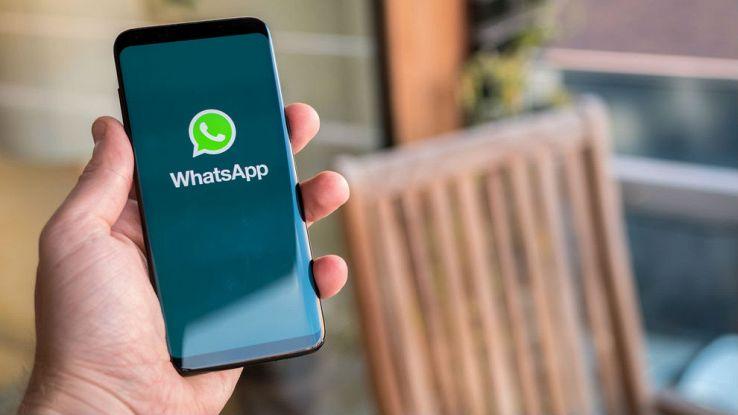Un utente tiene in mano il proprio smartphone con l'immagine di WhatsApp sullo schermo