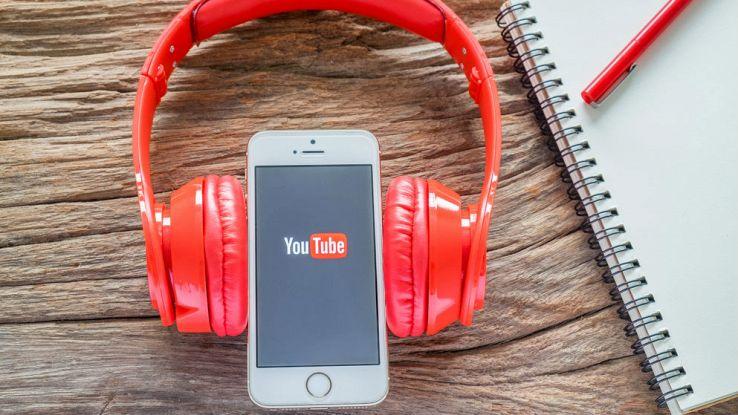 Uno smartphone con un paio di cuffie rosse su una scrivania con una penna e un block notes
