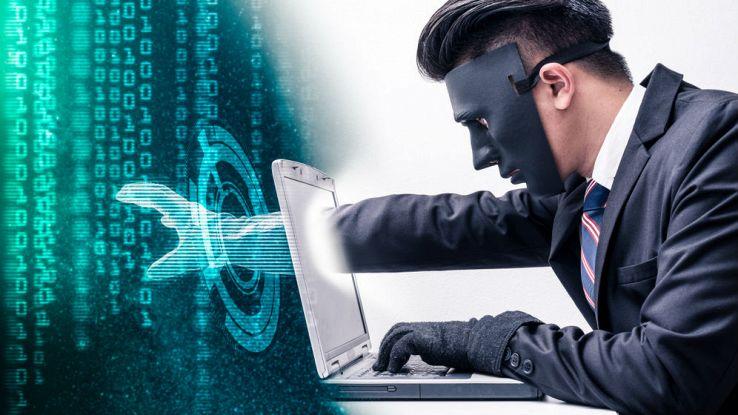 Un uomo con la maschera manomette un computer