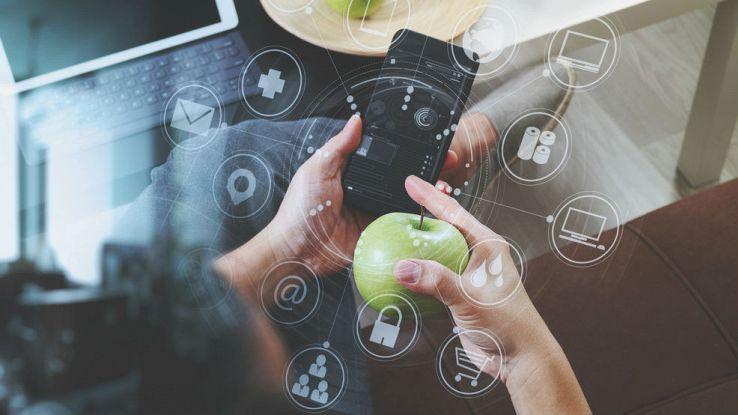 Un utente tiene in mano un iPhone e una mela