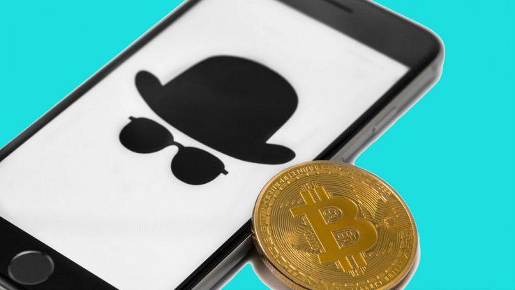 Un iPhone con una moneta di Bitcoin vicino allo schermo