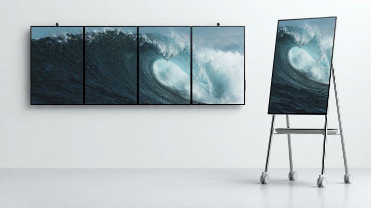 Quattro schermi Surface Hub 2 in fila più un Surface Hub 2 su un cavalletto