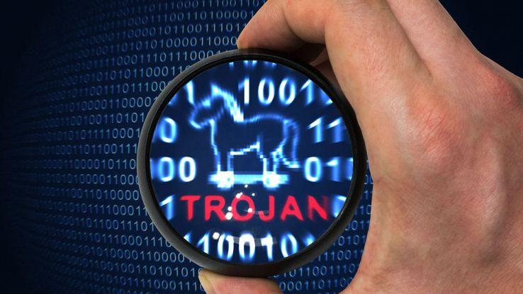 Una mano evidenzia con una lente una parte di codice e mette in evidenza la scritta Trojan