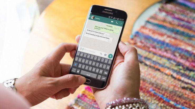 Un utente usa WhatApp a due mani con il proprio smartphone