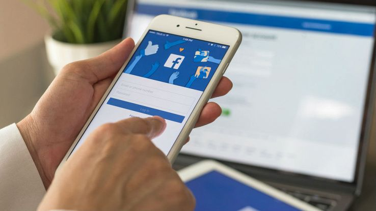 Un utente usa uno smartphone e un pc connessi a Facebook