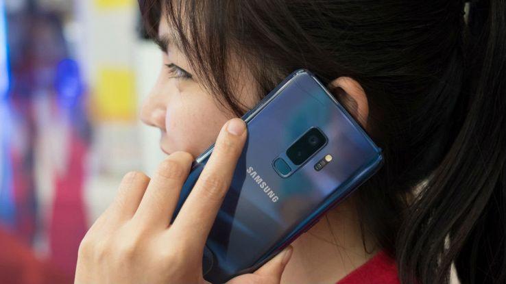Una donna effettua una chiamata dal proprio smartphone