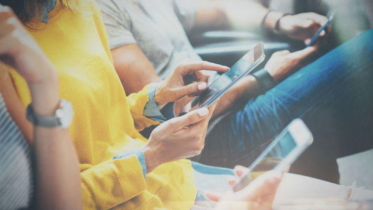 Tre persone usano il proprio smartphone mentre sono seduti