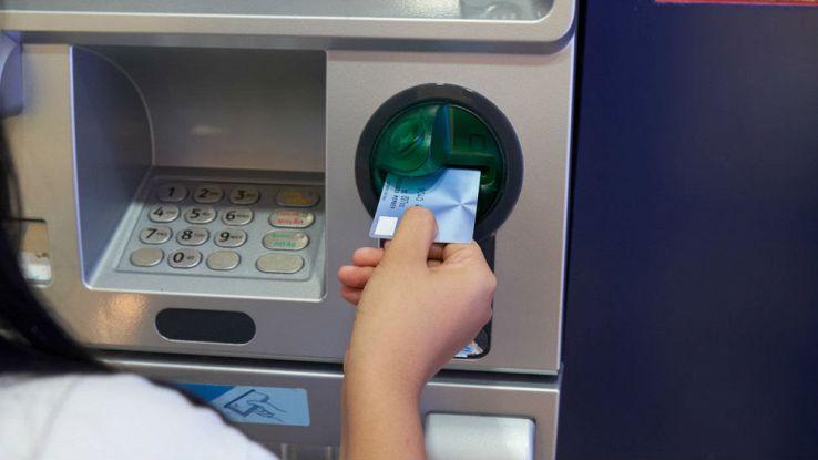 Una donna inserisce la propria carta di credito su uno sportello ATM