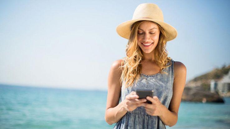Una donna legge l'email in spiaggi