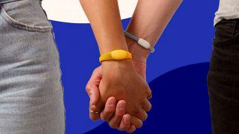 due persone si tengono per mano e indossano un wearable